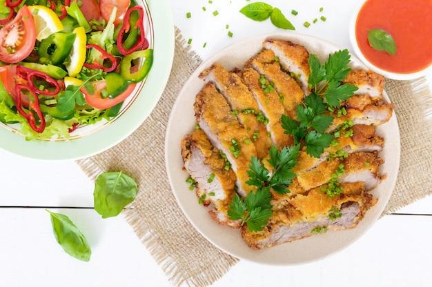 ゴールデンシュニッツェルのみじん切りスライスと白い木製のテーブルに野菜サラダのボウル。上面図。健康的なダイエット。