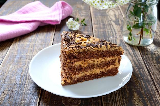 Шоколадный торт с ореховым кремом на деревянном столе. кусок торта на тарелке