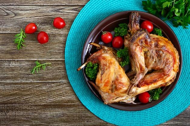 緑とトマトの皿の上の全体焼きウサギ。美味しい食肉。平面図、フラットレイアウト。