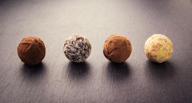 Шоколадный трюфель, трюфельные шоколадные конфеты с какао-порошком. коллекция шоколадных конфет. ассорти из шоколадных трюфелей с какао-порошком, кокосовым орехом и нарезанным фундуком на десертной тарелке.