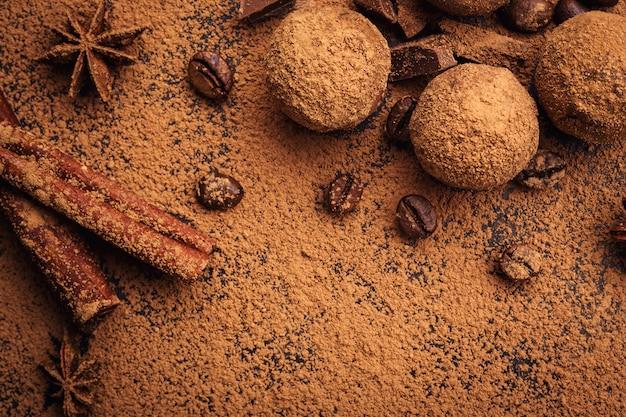 Шоколадный трюфель, трюфельные шоколадные конфеты с какао-порошком. домашние свежие энергетические шарики с шоколадом. ассорти из изысканных трюфелей, приготовленных шоколадом. кусочки шоколада и кофейных зерен