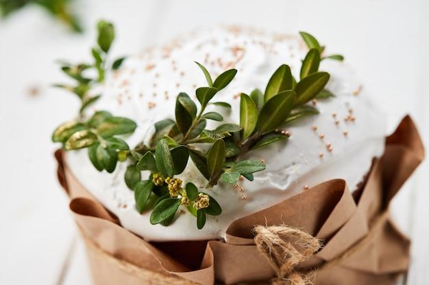 白い木製の背景、伝統的なクリーチ、パスカのお祝いの準備ができて艶をかけられたイースターケーキ