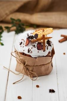 白い木製の背景、伝統的なクリーチ、パスカのお祝いの準備ができてのドライフルーツとシナモンスティックで飾られたイースターケーキ