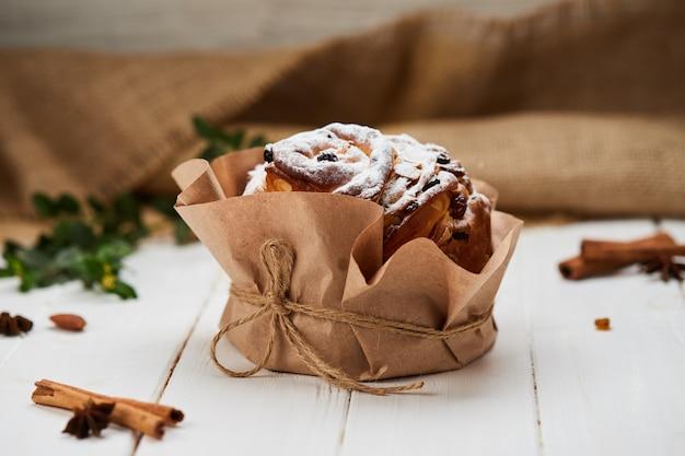 白い木製の背景、伝統的なクリーチ、パスカのお祝いの準備ができてレーズンと粉砂糖で飾られたイースターケーキ