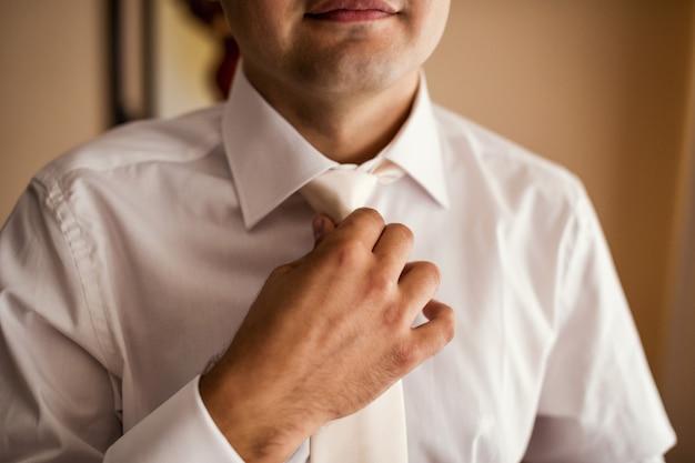 シャツを着せると自宅で首にネクタイを調整する男