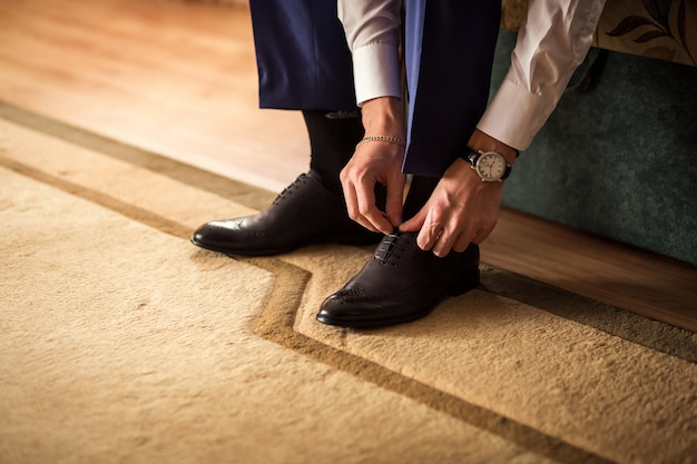 ビジネスマンの服の靴、仕事の準備をしている男、新郎の朝の結婚式の前に