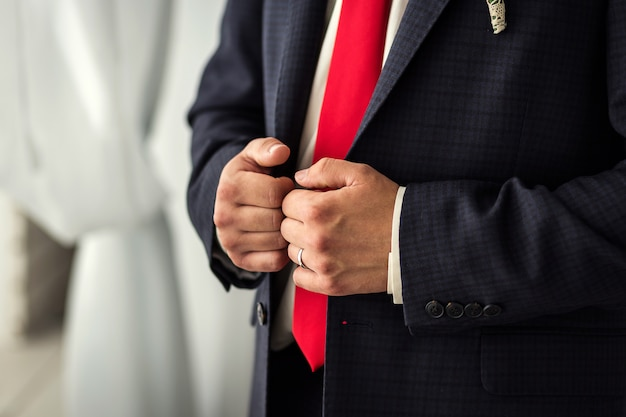 ビジネスマンはジャケットを着ています。政治家、男性のスタイル、男性の手のクローズアップ、ビジネスマン、ビジネス、ファッション、服のコンセプト