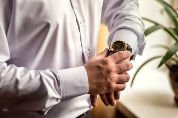 実業家は彼の腕時計、手に時計を置く男、新郎は結婚式の前に朝の準備の時間をチェック