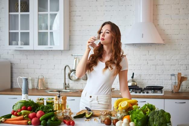 Молодая женщина, пить свежую воду из стекла на кухне. здоровый образ жизни и еда. здоровье, красота, диета концепции.