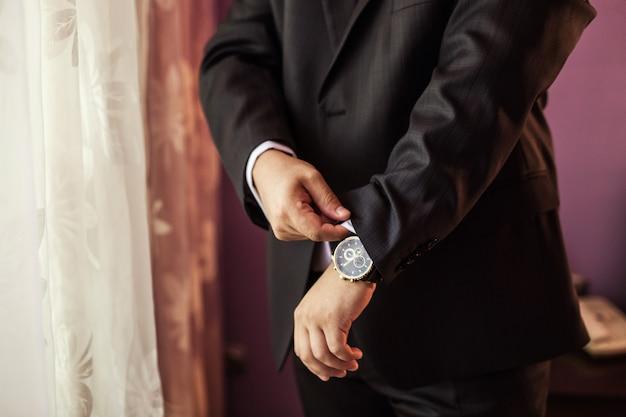 Бизнесмен, проверка времени на его наручные часы, человек ставит часы под рукой, жених готовится утром перед свадебной церемонией