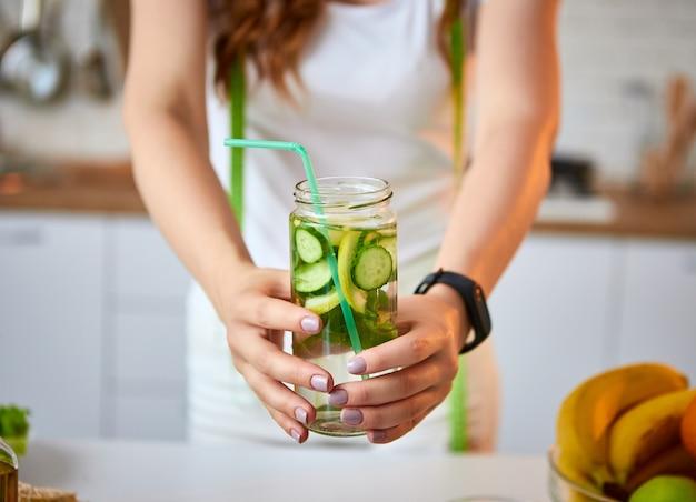 Молодая женщина, пить пресную воду с огурцом, лимоном и листьями мяты из стекла на кухне. здоровый образ жизни и еда. здоровье, красота, диета концепции.