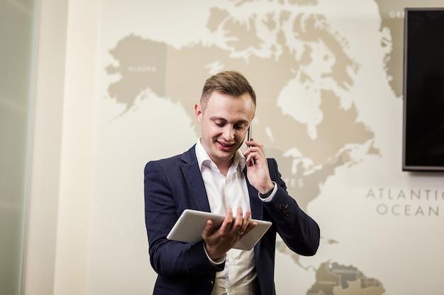 デジタルタブレット、オフィスでタブレットを使用してハンサムな若い男の肖像を保持しているビジネスの男性のイメージを閉じます。インフォグラフィックでタッチパッドを保持しているインテリジェントで自信を持ってのビジネスマン