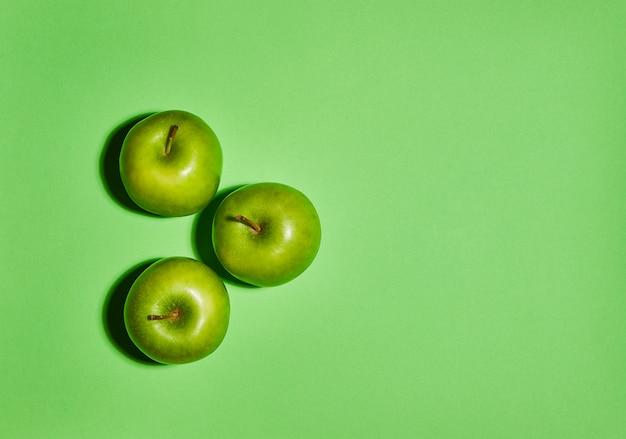 Свежие яблоки на зеленом фоне