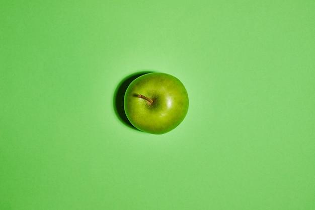 Свежее яблоко на зеленом фоне