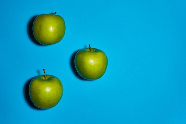 Свежие яблоки на синем фоне