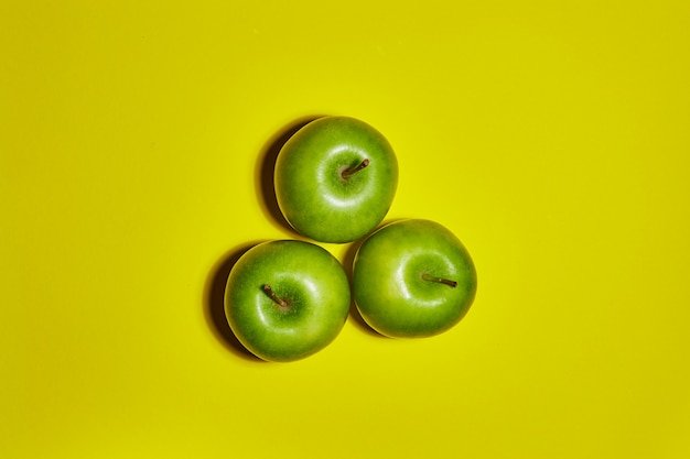 Свежие яблоки на желтом фоне