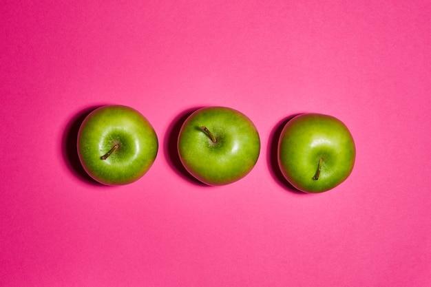 Свежие яблоки на розовом фоне