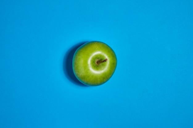 Свежее яблоко на синем фоне