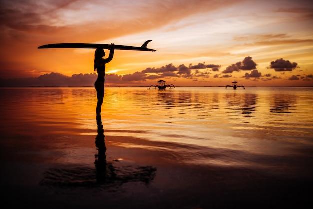 インド洋でサーフィンを泳ぐためのダイビングスーツで美しい女性