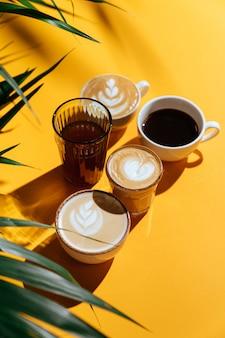 カラフルな背景とヤシの枝の朝のコーヒー。コピースペースで背景をぼかした写真。