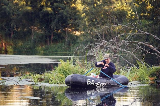 男はボートでパイクを釣り