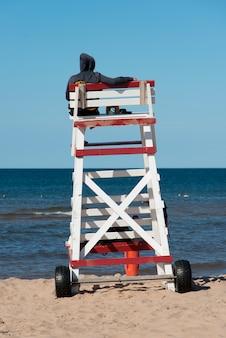 ライフガードは、カナダのプリンスエドワード島のグリーンゲーブルズのキャベンディッシュビーチに立っています。
