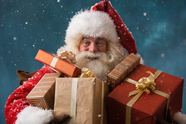 子供たちに贈り物をしている雪の中で屋外の幸せなサンタクロースの写真
