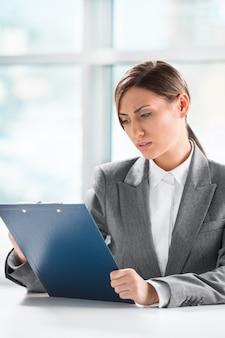 彼女のオフィスでクリップボードに論文を探しているビジネス女性の正面眺め