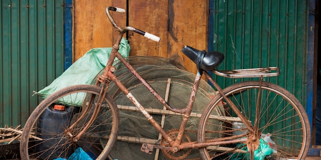 シェムリアップ、カンボジア、漁網に傾いた錆びた自転車