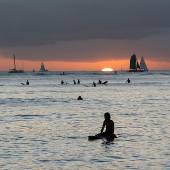 ワイキキ、ホノルル、オアフ島、ハワイ、アメリカ合衆国、日没時に海でサーフィンをする人々