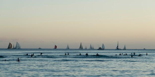 ワイキキ、ホノルル、オアフ島、ハワイ、米国、日没時の海のサーファーとヨット