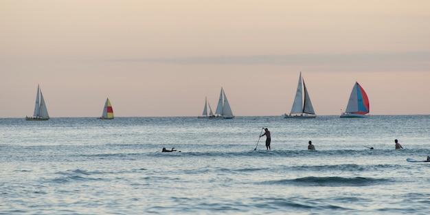 ワイキキ、ホノルル、オアフ、ハワイ、米国、バックグラウンドでヨットを持つサーファー