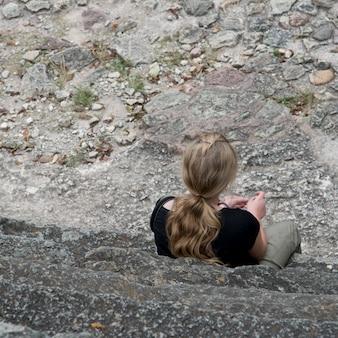 Женщина, сидящая на ступеньках в археологическом месте, копан, копан руинас, копан, гондурас