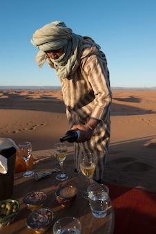 ツアレグ・マン、エルグ・チガガのワイングラスでワインを注いでるサハラ砂漠のラグジュアリー・デザート・キャンプ、スース・マッサ