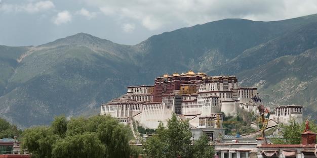 Вид на дворец потала с горами на заднем плане, лхаса, тибет, китай