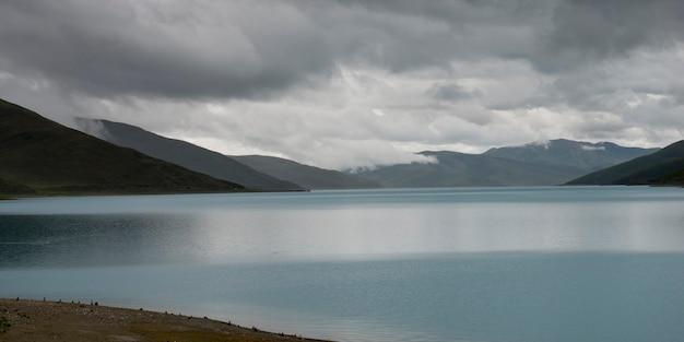 山岳地帯、曇った空、ナガルゼ、シャノン、チベット、中国の下に山々がある湖