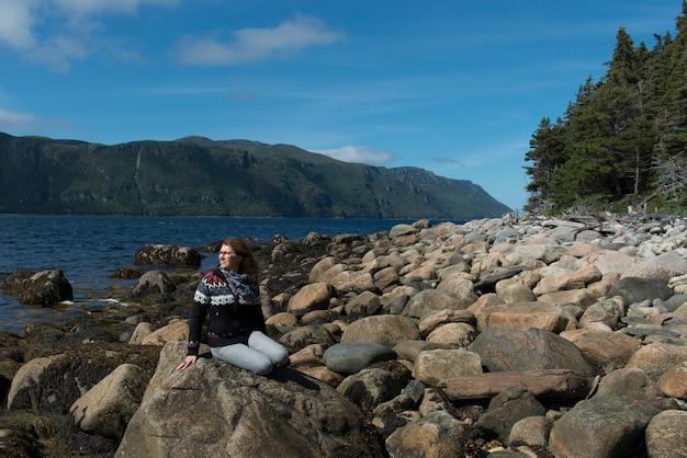 海岸、ノリスポイント、ボンベイ、グロス・モーン国立公園、ニューファンドランド島の岩に座っている女性そして