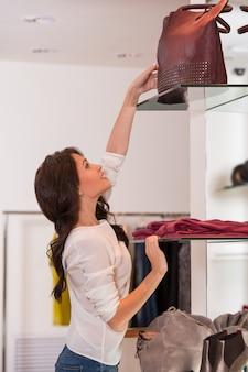 Молодая красивая женщина, достигая мешок на высокой полке в магазине во время покупок