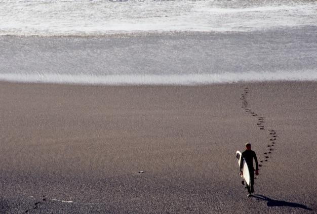 ビーチで歩く男、高い眺め