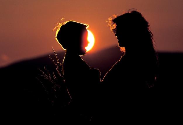 太陽と夕日を背景に話す母と息子のシルエット