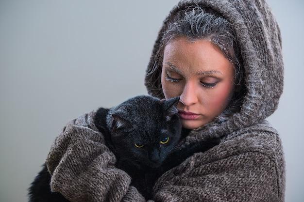 Зимний портрет молодой доброй женщины с большой черной кошкой