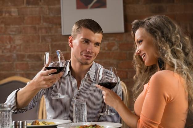 レストランでロマンチックな日付を持つ若い幸せなカップル
