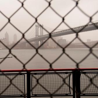 ニューヨーク、マンハッタンのチェーンリンクフェンスを通るマンハッタン橋