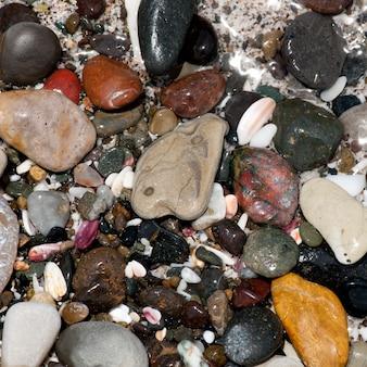 コスタリカの海岸線沿いの色の石と小石
