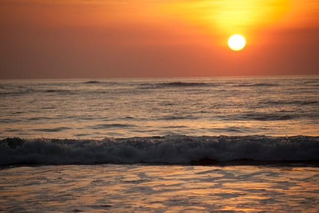 オレンジ色の輝きを放つ静かな海の日差し
