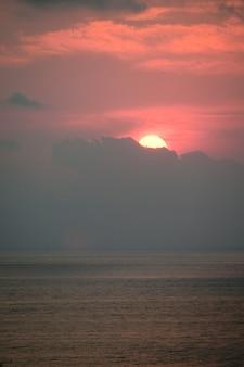 雲の後ろに隠れる海の上の赤い夕日
