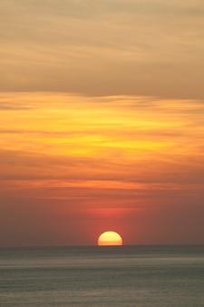 穏やかな海の地平線の上にオレンジ色の曇った夕日