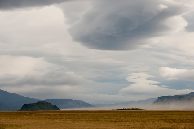 グレーの曇った空を持つ、山の前の不毛の牧草地の風景