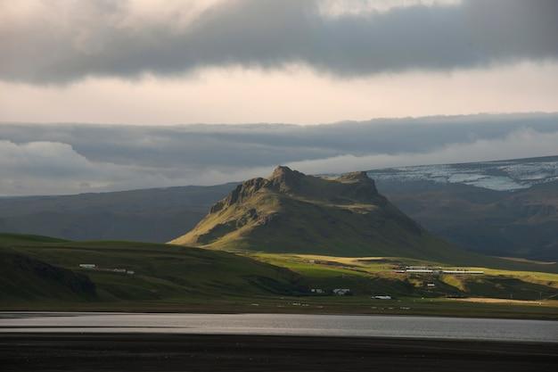緑色の草原の上に浮かぶ険しい山