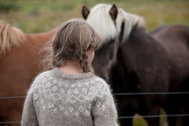Голова и спина девушки с грязными волосами в вязаном свитере перед исландскими лошадьми